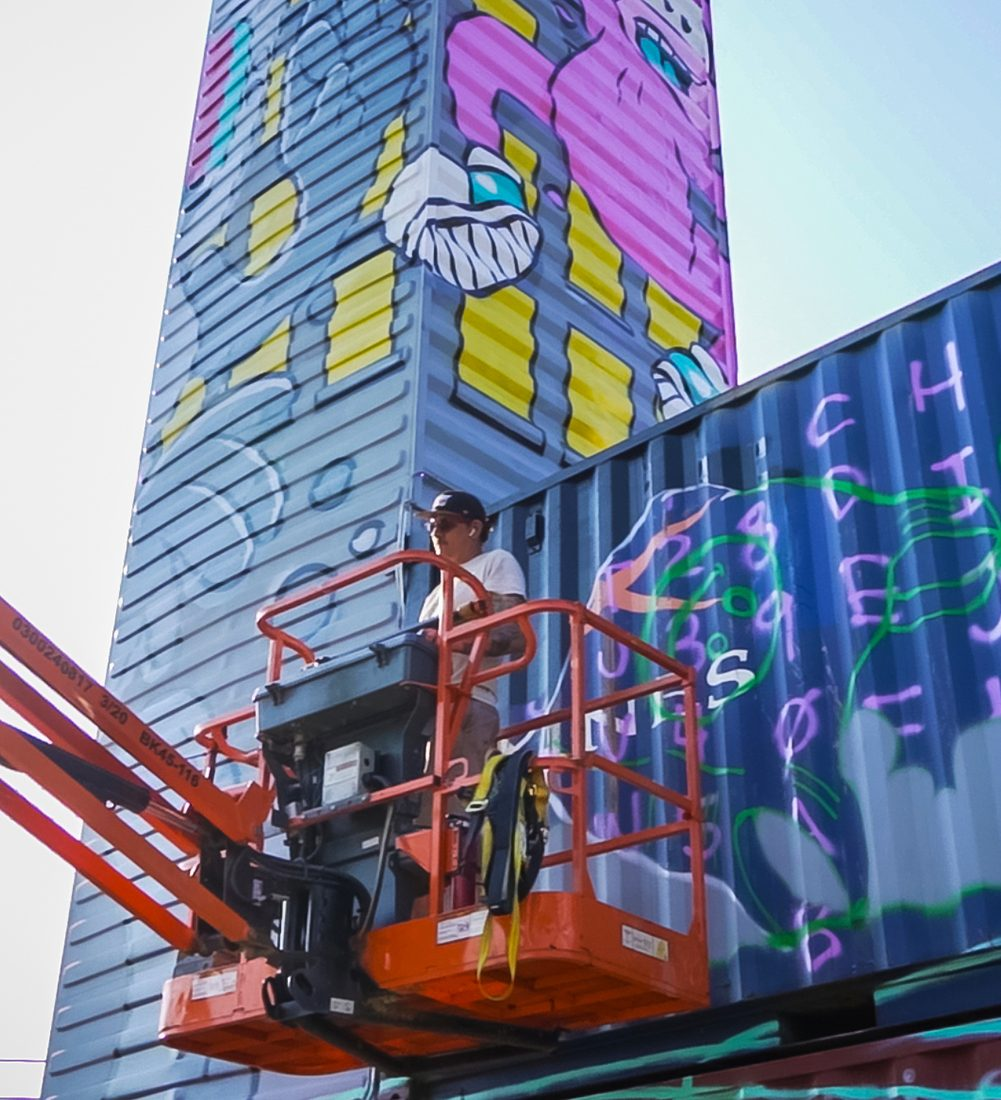 artist on a crane platform in front of 2 shipping container murals