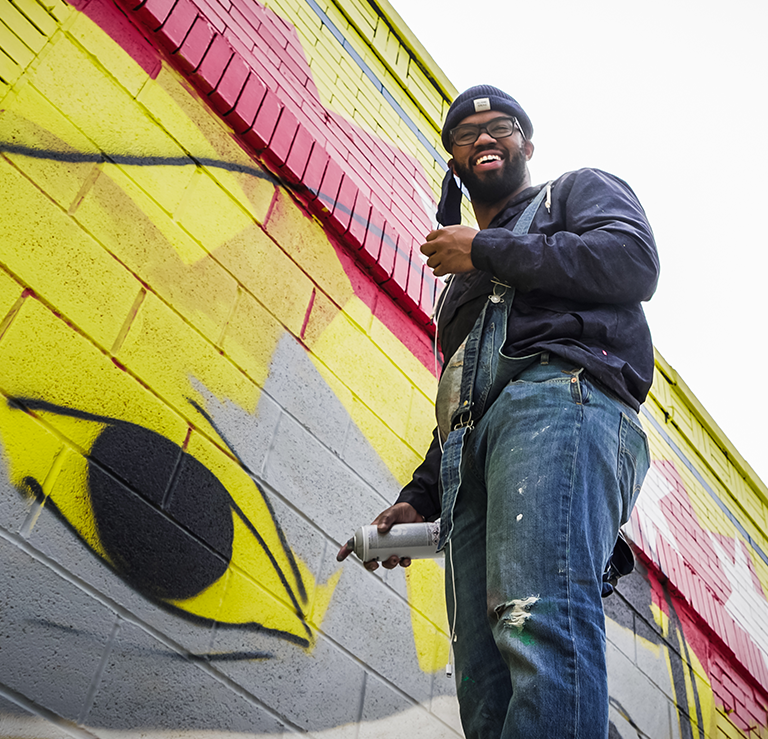 photo looking up from the ground at an artist painting a yellow eyeball on an outdoor mural on the side of a building