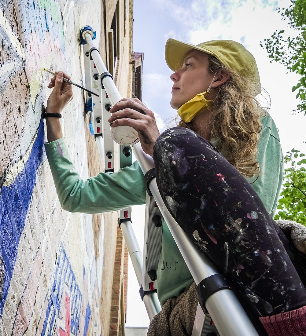 close up of mural artist using a small paintbrush to paint details on her outdoor building mural