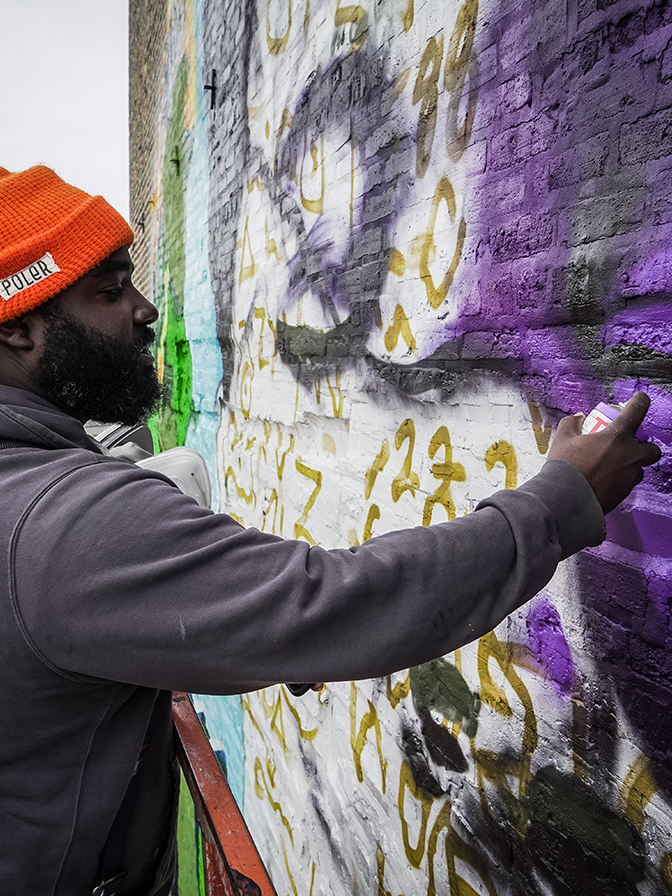 close up of artist painting purple spray paint on an outdoor mural on the side of a building