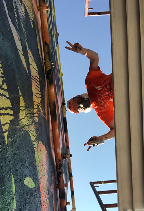 artist looking over the side of his platform crane giving a peace sign while working on an outdoor mural