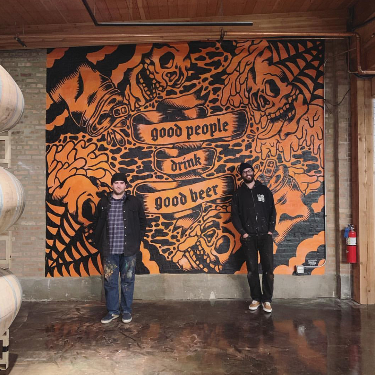 artists standing in front of interior wall mural